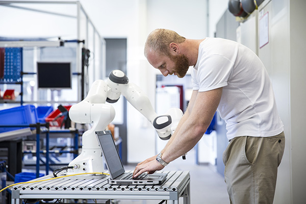 industry 4.0: Young engineer works at a robotic arm